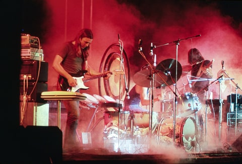 Pink Floyd playing on the stage surrounded with a smoke and illuminated with a red stage lights during the concert at Merriweather Post Pavilion, Columbia, Maryland in 1973.