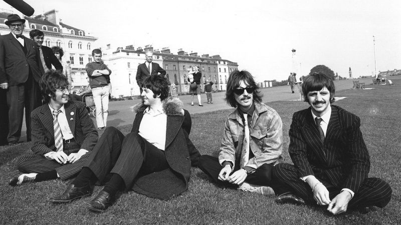 """The Beatles, (left to right) John Lennon, Paul McCartney, George Harrison and Ringo Starr, take a break during the filming of """"The Magical Mystery Tour"""" at Plymouth Hoe on Sept. 13, 1967."""