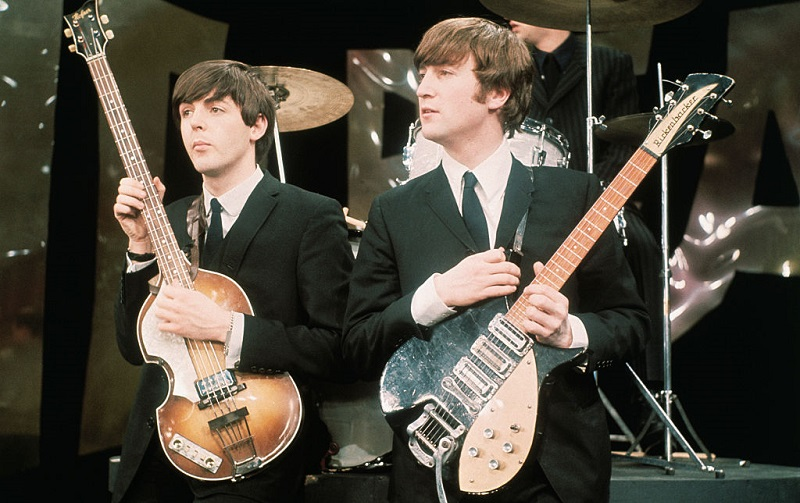 Paul McCartney and John Lennon with their instruments in 1964
